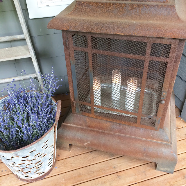 An Oversized Lantern with Candles and an Antique Olive Bucket
